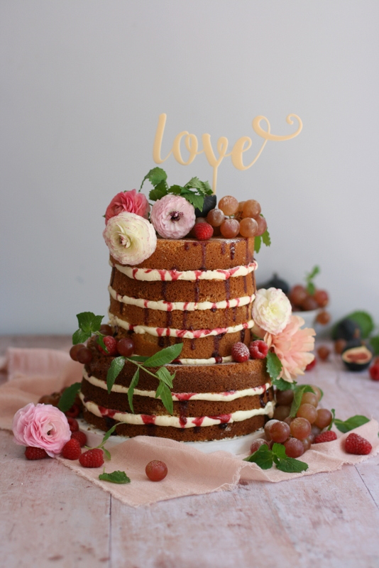 Two tier naked wedding cake for a summer wedding with ranunculus, grapes and berries