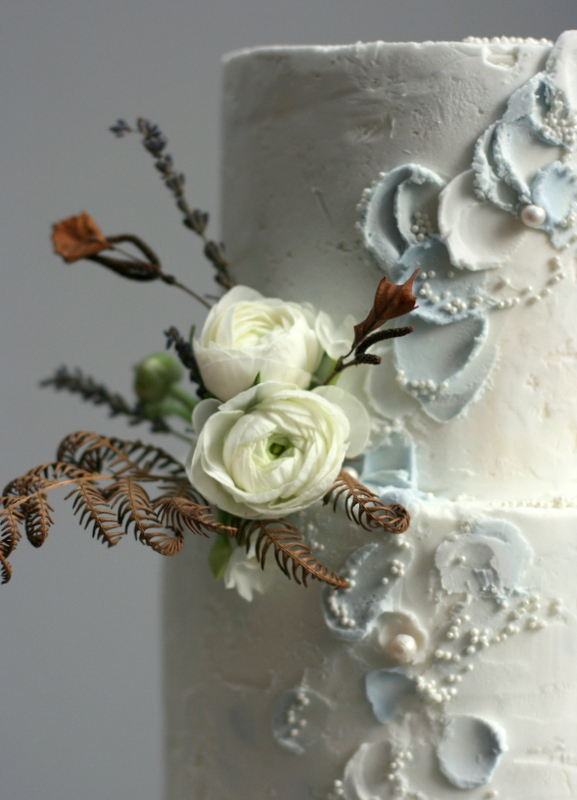 Textured buttercream wedding cake with fresh ranunculus and dried bracken
