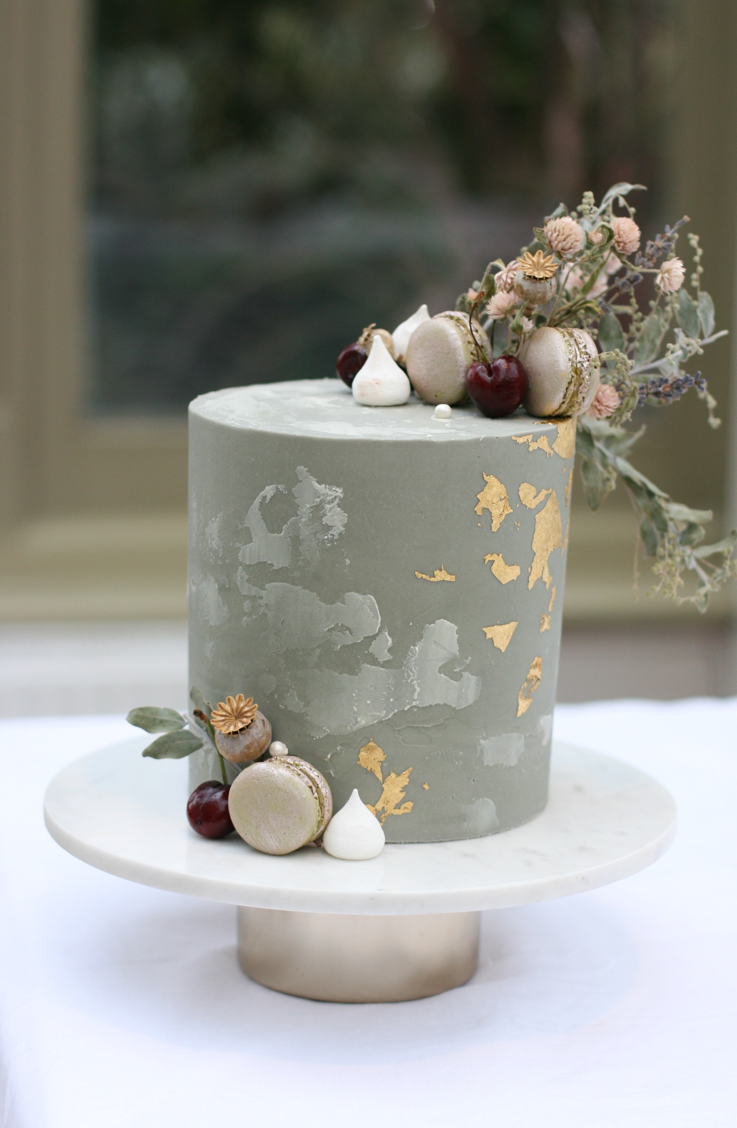 Grey concrete effect buttercream wedding cake with modern details of edible gold leaf, metallic macaron, mini meringue kisses and dried flowers