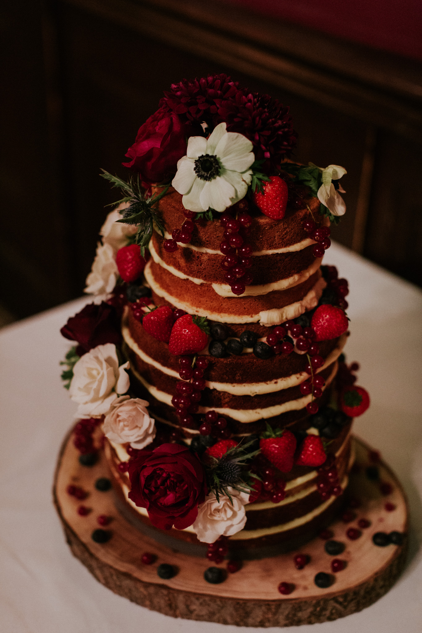 Winter naked wedding cake decorated in seasonal red and white flowers. Photo by Maja Tsolo
