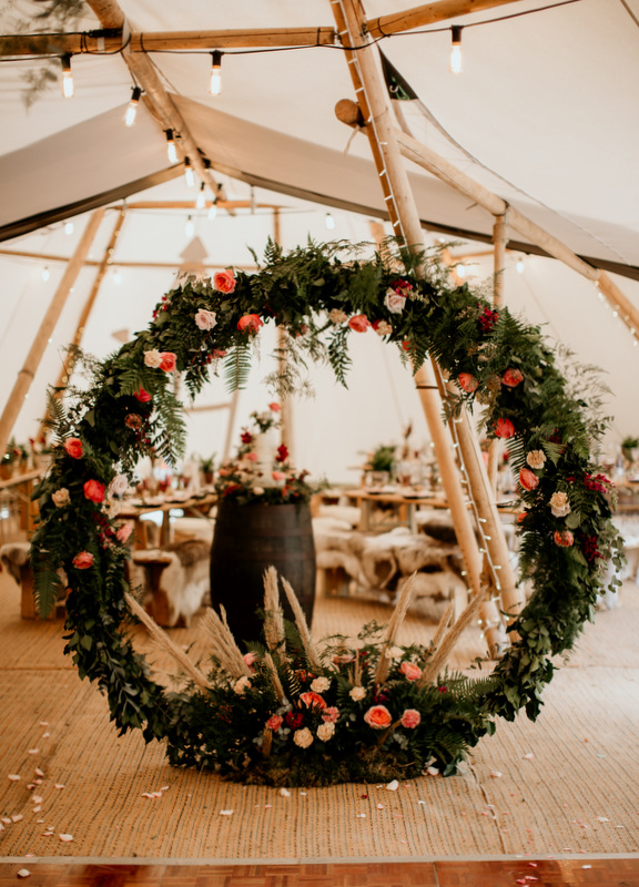 Lots and lots of wildflowers in this floral moongate framing buttercream wedding cake in Surrey tipi wedding. Photo by Elena Popa