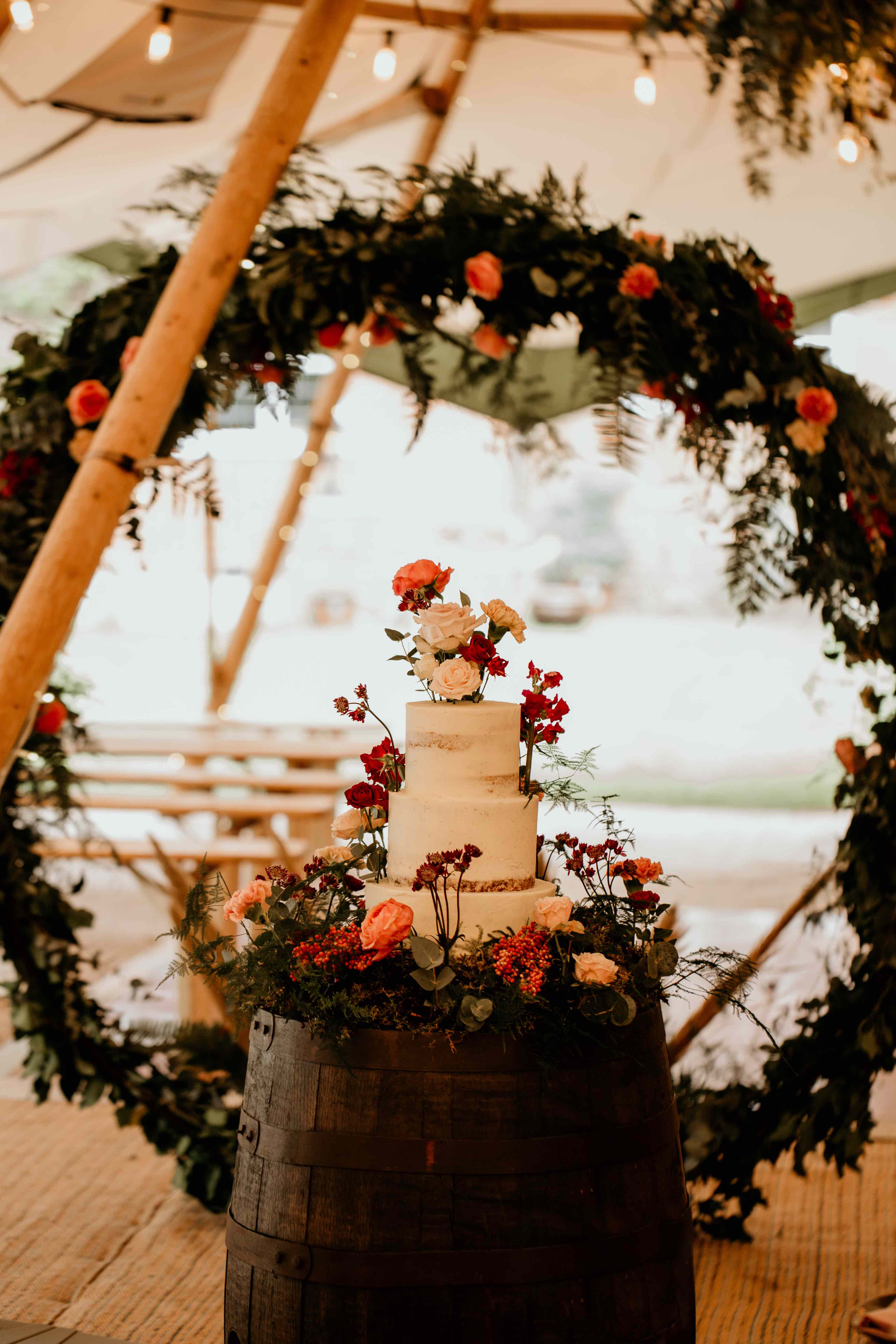 Floral buttercream wedding cake for luxurious tipi wedding in Surrey. Photo by Elena Popa