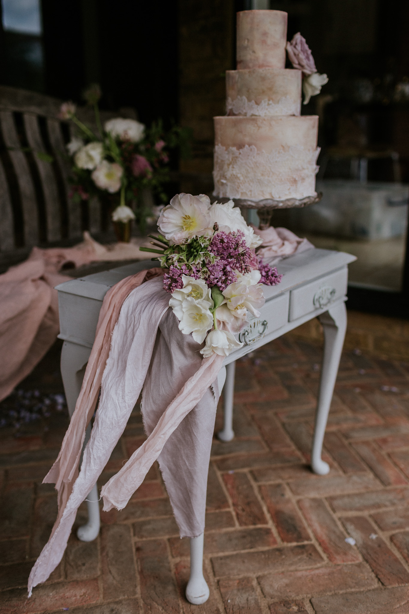 Three tier textured buttercream wedding cake with edible lace and rose gold tones. Photo by Maja Tsolo