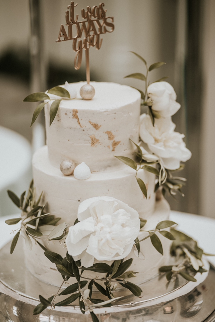 Beautiful buttercream wedding cake decorated with gold accents, white peonies and greenery. Buxted Park Hotel, Sussex. Photo by Nataly J Photography