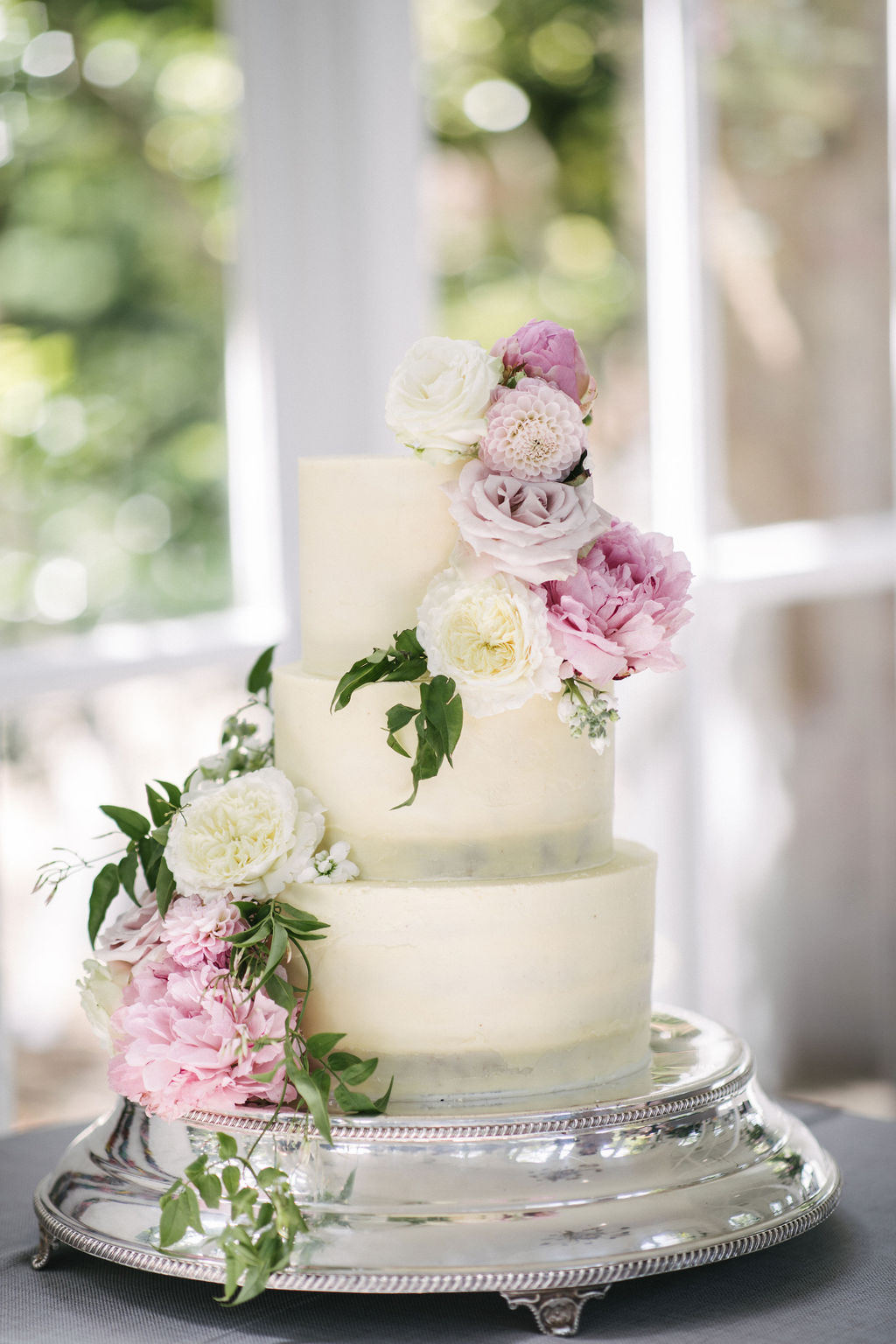 Modern elegant buttercream wedding cake decorated with Spring flowers. Photo by Kari Bellamy