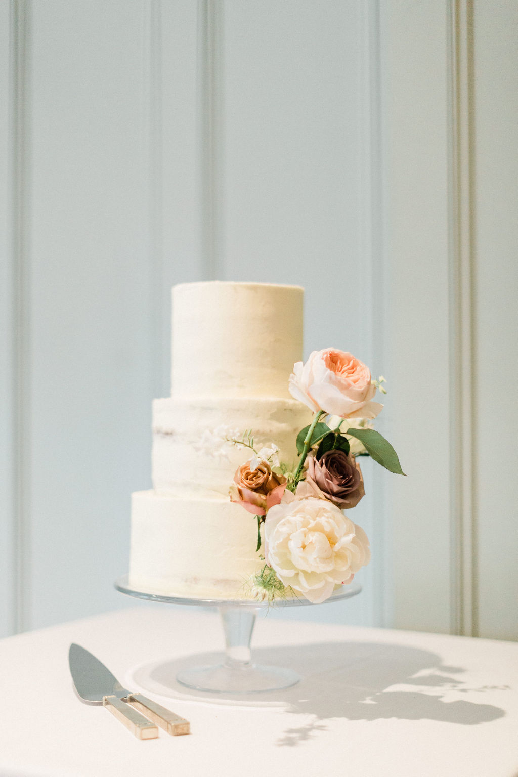 Understated, simply beautiful buttercream wedding cake decorated with a flourish of fresh flowers. Photo by Jacob & Pauline