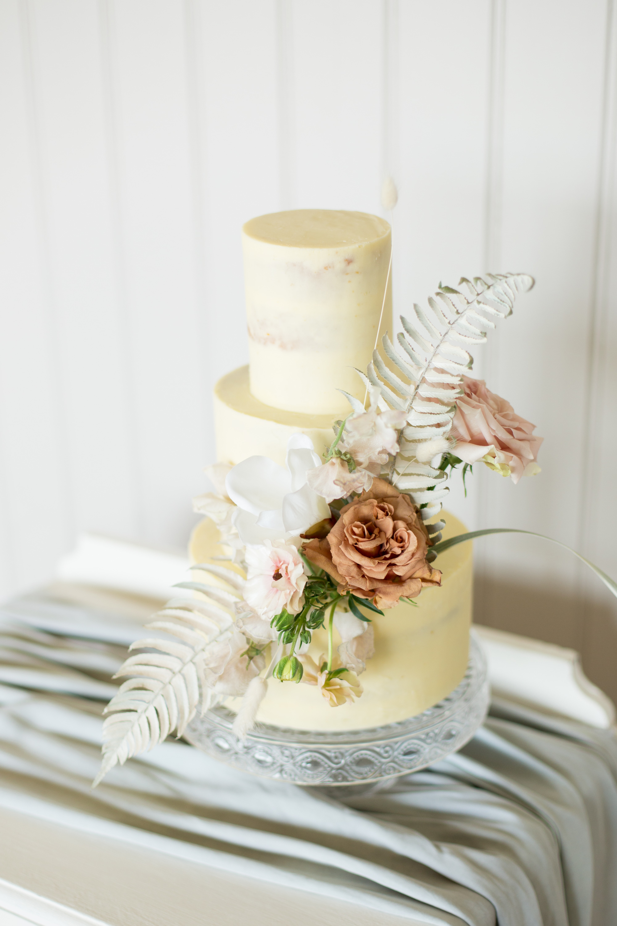 Sleek, smooth buttercream cake decorated with striking florals with dried palms, butterfly ranunculus and pretty toffee coloured roses