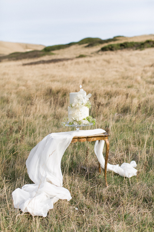 Two tier romantic buttercream wedding cake at Lulworth Cove