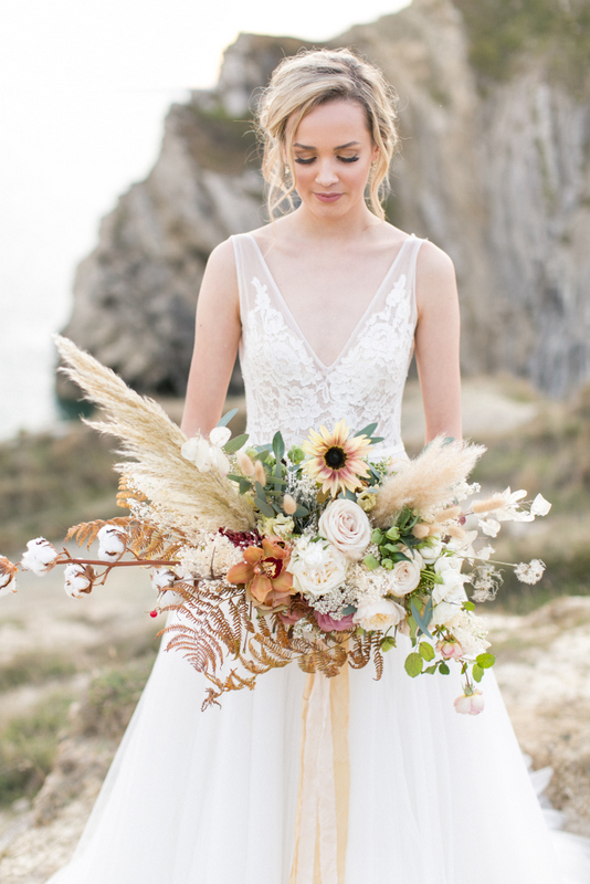 Bride and flower bouquet at Lulworth Cove, Somerset. Photo by Anneli Marinovich